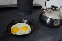 """Tea and cast iron fried eggs over a wood burning stove"" Wellington, Prince Edward County, Ontario"