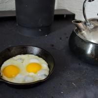 """Tea and cast iron fried eggs over a wood burning stove"" Wellington, Prince Edward County, Ontario"